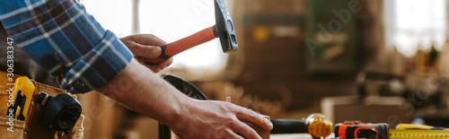 panoramic shot of carpenter holding hammer in workshop Wallpaper Mural