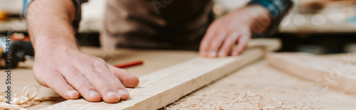 Canvas Print panoramic shot of carpenter touching wooden plank