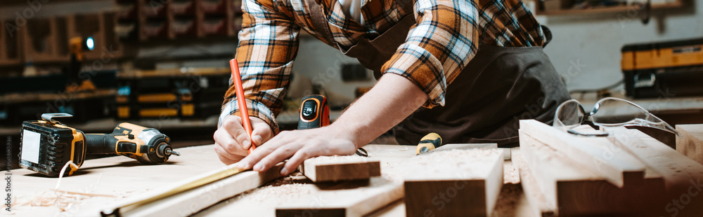 Fototapeta panoramic shot of woodworker measuring wooden plank