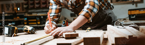 Fotografering panoramic shot of woodworker measuring wooden plank