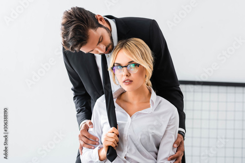 Sexy businesswoman pulling tie of businessman in office Wallpaper Mural