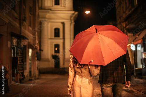 Fotografía back view of couple in autumn outfit walking under umbrella along evening street