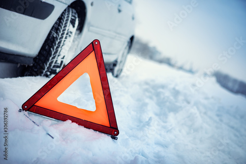 fototapeta na szkło Close up of red warning triangle with a broken down car in winter