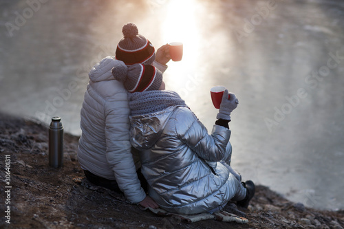Fotografie, Obraz  Couple drinking hot coffee or tea and sitting next to stunning winter landscape