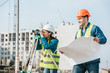 Smiling surveyor with blueprint and colleague with digital level