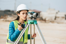 Female Surveyor With Radio Set Looking Through Digital Level