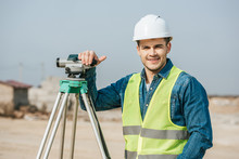 Smiling Surveyor With Digital Level Looking At Camera