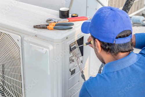 Fototapeta a professional electrician man is fixing a heavy duty unit of central air conditioning system by his tools on the roof top and wearing  uniform and white cap obraz