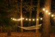 canvas print picture - A hammock is strung up between two trees surrounded by cafe lights with starbursts; romantic peaceful evening