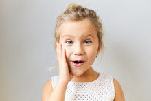 Adorable European Girl Of Preschool Age Posing Isolated With Hand On Her Cheek, Saying Wow With Mouth Opened, Being Amazed With Exciting News, Expressing True Reaction, Wearing Dotted Dress