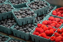 Punnets Of Raspberries And Blueberries For Sale On A Market Stall