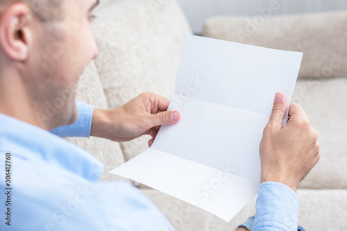 Man reading a letter at the couch, men's hands, close up, rear view, copy space, Canvas Print