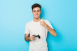 canvas print picture - Young caucasian man playing videogames with game controller smiling and raising thumb up