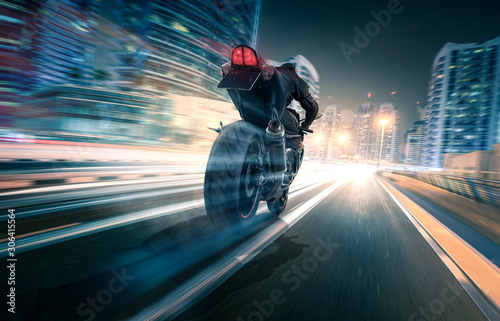 Motorrad fährt durch eine Stadt bei Nacht