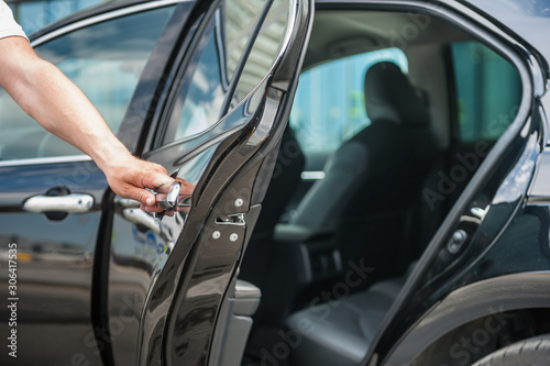 Canvas Close up man opens car's door.