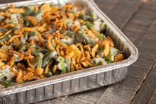 Traditional Green Bean Casserole With Fried Onions On A Wooden Table