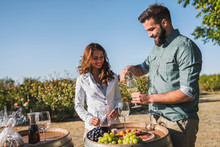 Young Smiling Man And Woman Tasting Wine At Winery Vineyard - Young People Enjoying Harvest Time Together