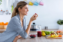 Pretty Young Woman Eating Red Berries While Sitting In The Kitchen At Home.