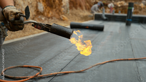 CLOSE UP: Builder holds a burning blowtorch after hydroisolating a building Canvas Print