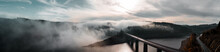 Aerial Drone View From Above Of A Morning Mountain Landscape With A Lake Dam And Heavy Low Fog Clouds Hanging Over The Water And Hills And Winter Mood.