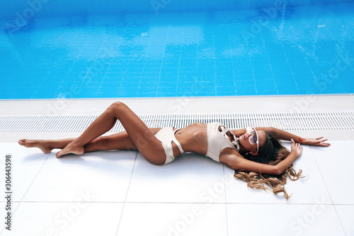 Obraz beautiful sensual woman with blond hair in elegant swimming suit relaxing in luxurious white villa - fototapety do salonu
