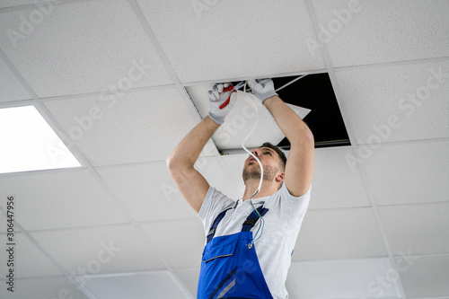 Fotomural  Electrician On Stepladder Installs Lighting To The Ceiling