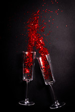 Glass With Red Glitter Over Black Background, Holiday Concept Flat Lay