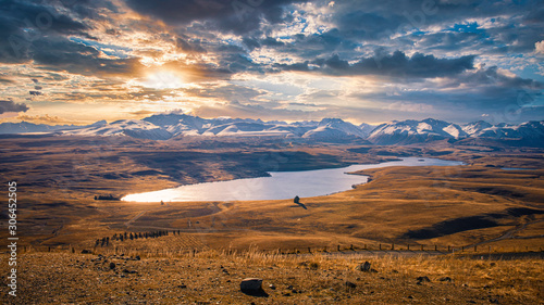 Lake Alexandrina surrounded by tawny tussock and snowy peaks, hidden gem in the Wallpaper Mural