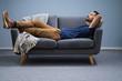 Leinwanddruck Bild - Man Relaxing On Sofa At Home