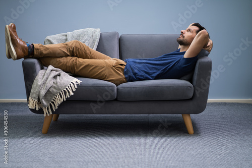 Man Relaxing On Sofa At Home Billede på lærred