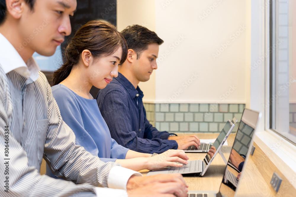 Fototapeta 長テーブルで並んで仕事をする男性と女性