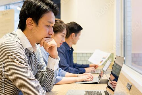 長テーブルで並んで仕事をする男性と女性 Wallpaper Mural