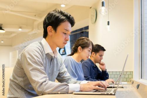 Photo 長テーブルで並んで仕事をする男性と女性