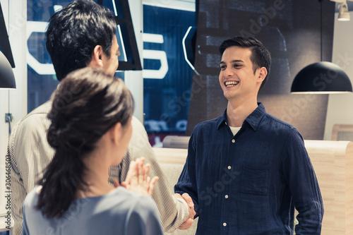 握手をする男性と見守る女性 Fototapet