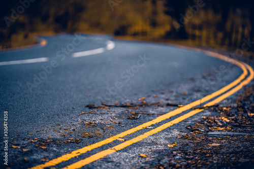 Curvy road in autumn with fall colors and bokeh (blurred background) in a forest Wallpaper Mural