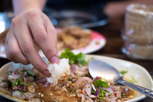 Close Up Fingers Hand Eating Sticky Rice Spicy Minced Pork Salad In White Dish, Dipping Sauce Mix Pork Herb Spicy Thai Style Traditional Isan (Northeastern Thailand)