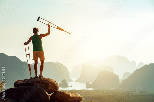 Foto Disabled man with crutches stands on big rock
