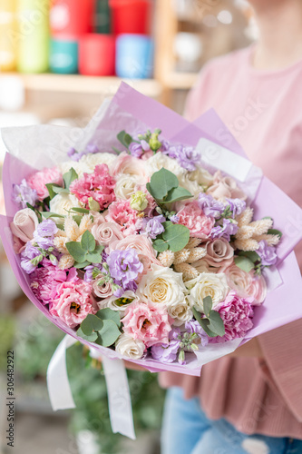 European floral shop. Beautiful bouquet of mixed flowers in womans hands. the work of the florist at a flower shop. Delivery fresh cut flower. © malkovkosta