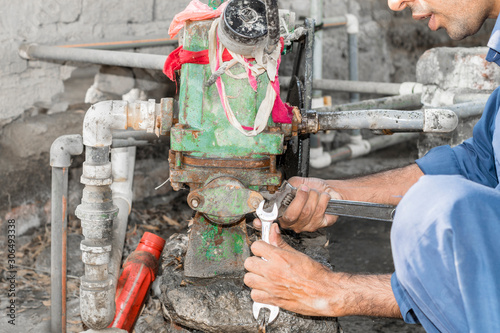 a professional an electrician man is examining an old water motor Canvas Print