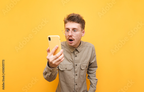 Shocked nerd guy in shirt looks at smartphone screen with surprised face, wears glasses and mustache isolated on yellow background Fototapet