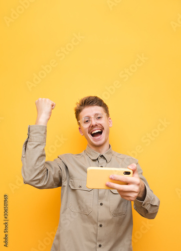 Fotografía  Happy guy in shirt and glasses and with smartphone in his hand emotionally rejoicing, looking at the camera and smiling