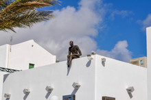 A Statue Of A Man Sits On The Roof Of The White Building In Greece, Santorini