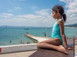 Jamaican European ethnicity little girl sitting on the empty wooden table on the sea beach and looking at the sea