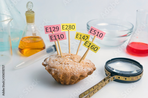 Fotografie, Obraz A cupcake decorated with name plates of additives E, test tubes and a magnifier stand nearby