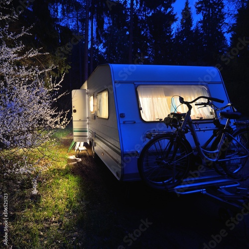Canvastavla Caravan trailer on a forest road under a blooming tree in Spring