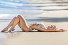 Beautiful Young Blonde Is Laying Near The Tropical Sea On The White Beach.