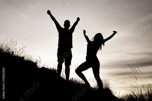 Photo Siluetas de una pareja (chico y chica) con las manos en alto mirándo hacia delante y de perfil en una puesta de sol mientras hacían deporte (trekking) por el monte (montaña) en Andalucia