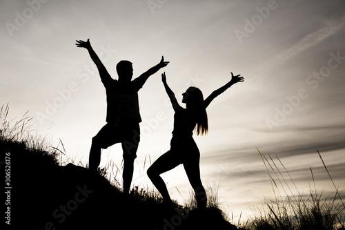 Siluetas de una pareja (chico y chica) con las manos en alto mirándose y de perfil en una puesta de sol mientras hacían deporte (trekking) por el monte (montaña) en Andalucia Canvas Print