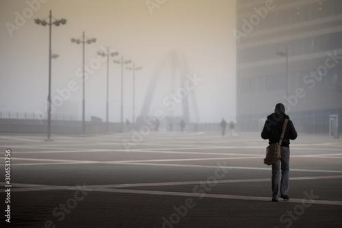 Photo Persona che cammina in una piazza di Milano con la Nebbia