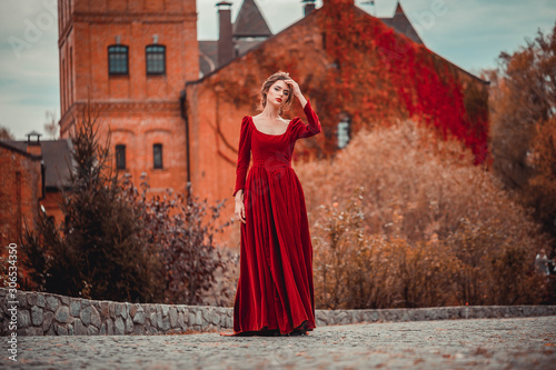 Beautiful girl in a burgundy red dress walking near  old castle on a background of autumn grape leaves in the park, October Fotobehang